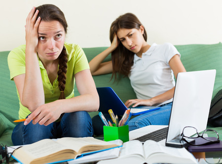 mournful: Dreary teenage student girls study at the home with books and computers