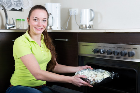 cheeful: Happy woman cooking fish  in oven at home kitchen