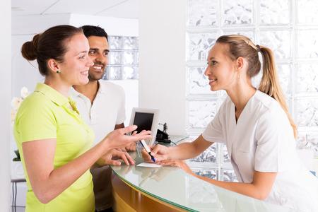planificacion familiar: Familia alegre en la sala de espera de la clínica de planificación familiar
