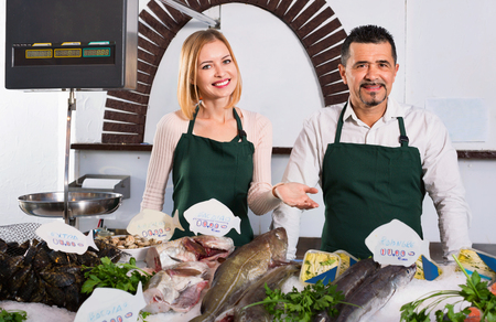 fish selling: Positive smiling shop assistants selling fresh fish and chilled seafood