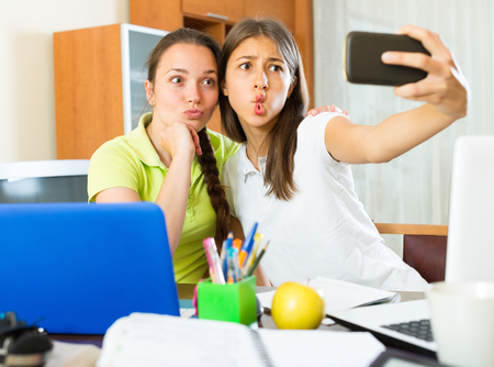 Portrait of two cheerful young girls doing selfie with smartphone at home