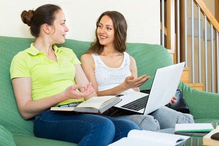cognate: Two young positive girls studying at home Stock Photo