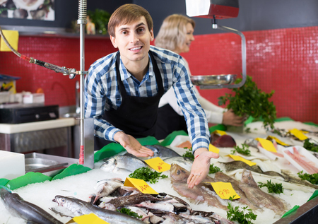 positive european  shop stuff selling chilled on ice fish in supermarket