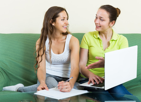 parsimony: Smiling women looking financial documents with laptop  in home  Stock Photo