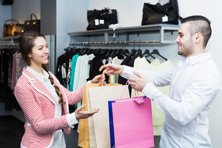 store clerk: Store clerk serving positive purchaser at fashionable apparel store Stock Photo