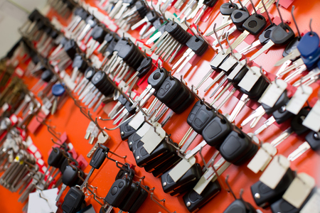 Car and van keys hanging on hooks at locksmith stand at workshop Stock Photo