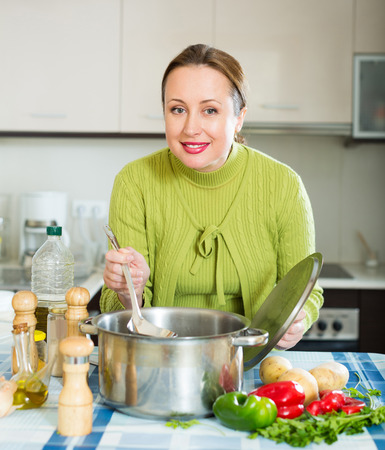 domestic kitchen: happy woman with ladle cooking soup in domestic kitchen