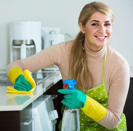 happy european blonde maid cleaning in domestic kitchen with sprayer