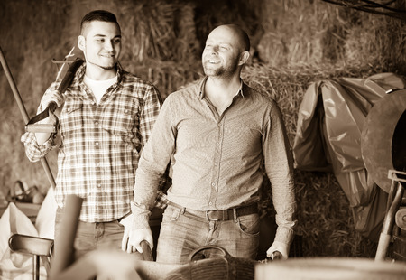 ranchers: Two smiling ranchers working in a granary