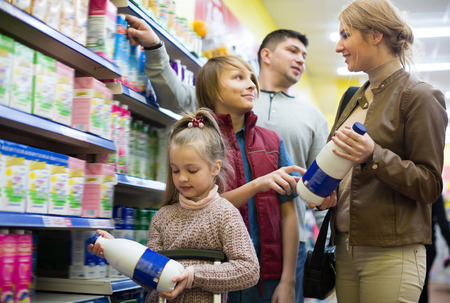 pasteurized: Happy family buying pasteurized milk in supermarket