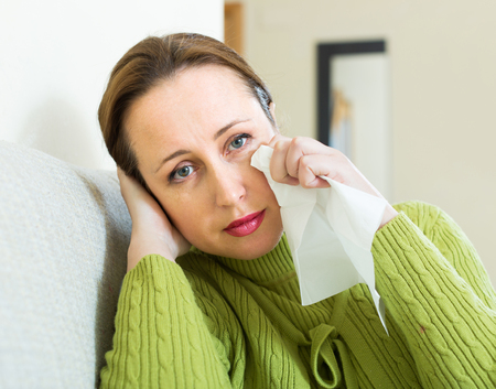 Sad and lonely woman crying on couch at home Stock Photo