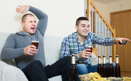 fandom: Two active male sport fans watching hockey game with beer heatedly at home Stock Photo