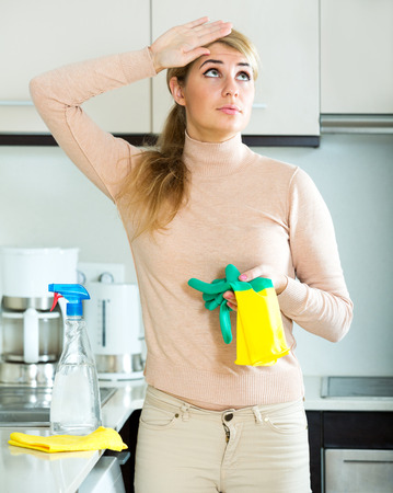 Sad adult woman in rubber gloves posing at kitchen