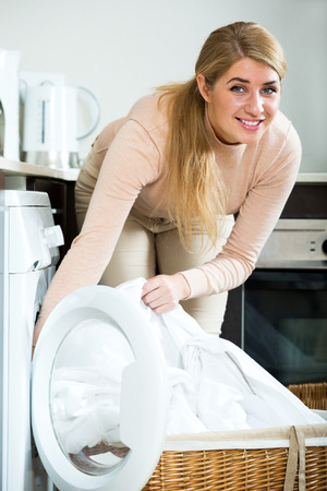 Portrait of attractive housewife satisfied with quality of washing
