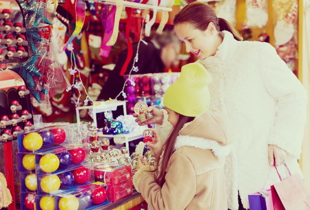 Happy mother with small daughter choosing souvenirs in Christmas market