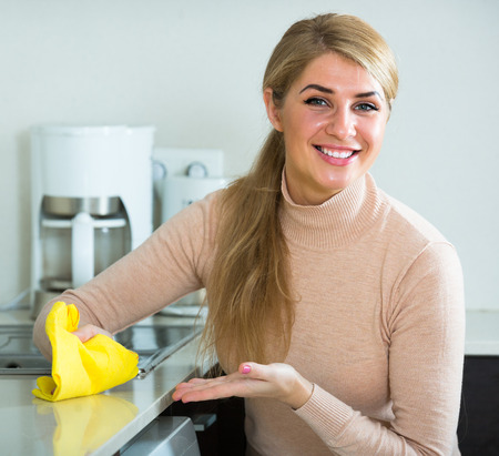 Portrait of smiling female houseworker with rag dusting in home kitchen