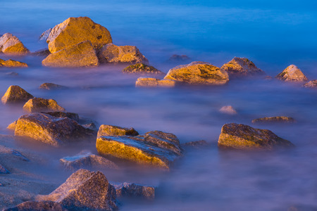 gloaming: Scenic view of river rocks in haze at twilight
