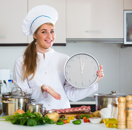 checking ingredients: Female chef showing time needed for preparing pork ribs