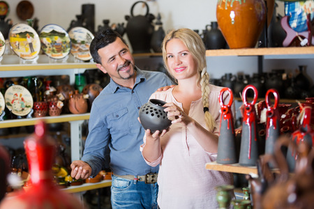 Couple in souvenir shop buying black ceramic bowl Stock Photo