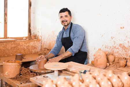 creating: smiling artisan man creating ceramic piece on spinning pottery wheel in workshop