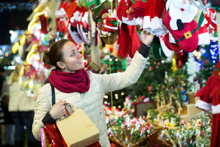 lifestile: Portrait of beautiful female customer near counter with Christmas gifts in evening time
