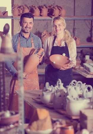 artisans: two cheerful artisans holding ceramics in hands and standing in workshop Stock Photo