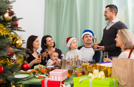 granny and grandad: big family with children celebrates Christmas at table in home