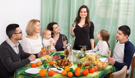 grandad: Happy multigenerational family sitting at holiday table, toasting and smiling