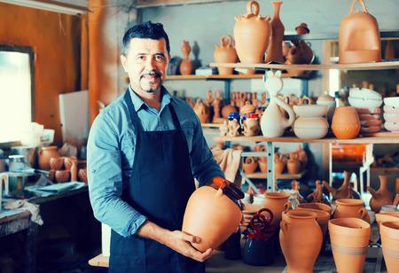 atelier: Smiling spanish man potter holding ceramic vessels in atelier Stock Photo