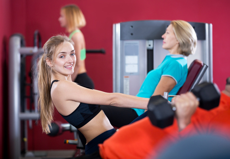Cheerful people of different age having strength training in sport club