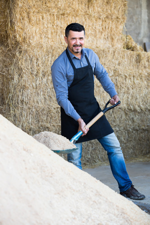 trenching: cheerful mature farm worker in apron holding big shovel on farm indoors Stock Photo