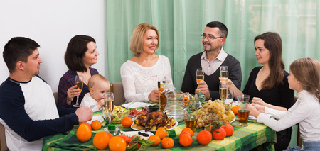 granny and grandad: Big positive family sitting at holiday table, toasting and smiling