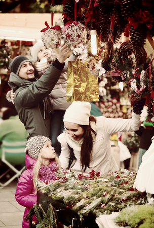 Happy family choosing x-mas decorations at market. Focus on woman and girl Stock Photo