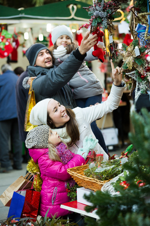 Positive young family of four choosing floral decorations at market. Focus on woman