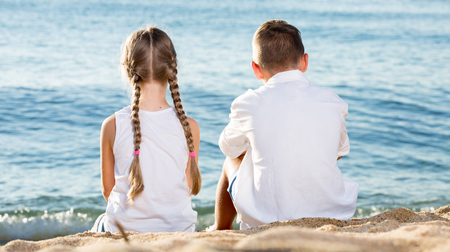 niños platicando: retrato de un niño y la niña sentada atrás adelante junto en la playa de arena en la luz del sol