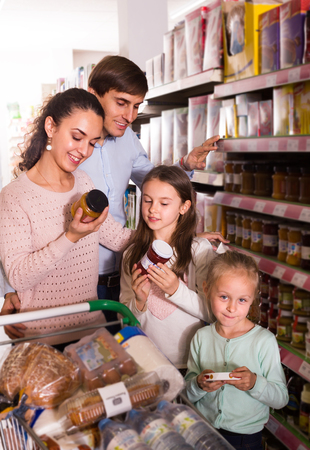 parents with kids choosing jar of confiture in store