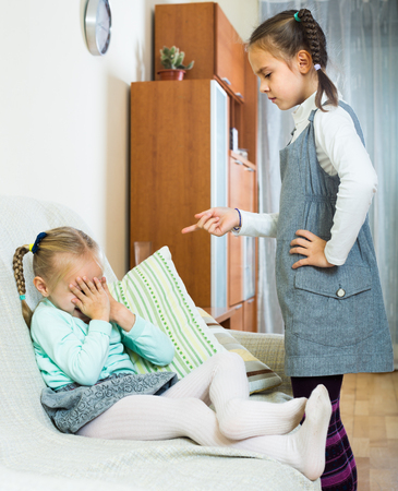 berate: big sister preaching little one and shaking finger Stock Photo