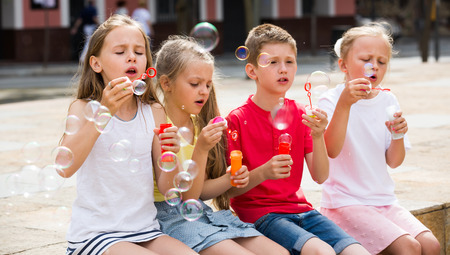 playful boy with little girlfriends in elementary school age blowing bubbles outdoors Stock Photo