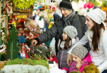 Ordinary happy family with little girls standing at coniferous souvenirs counter at fair. Focus on women
