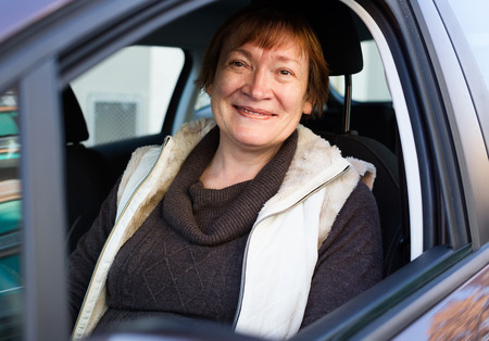 75s: Portrait of happy russian  female senior driver smiling in car Stock Photo