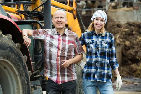 Happy farmers working at agricultural machinery in farm