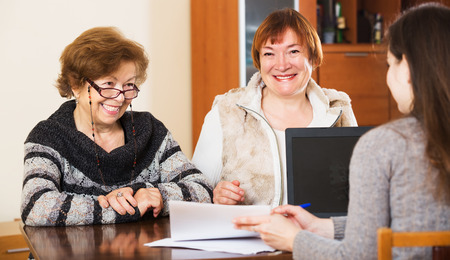 75s: Portrait of happy elderly women with papers and agency employee