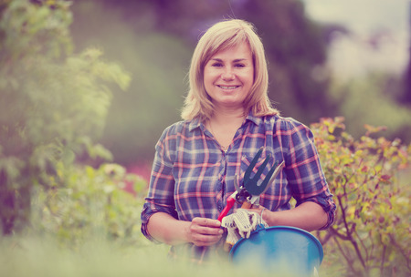 horticultural: glad blond mature woman having horticultural instruments in garden on summer day