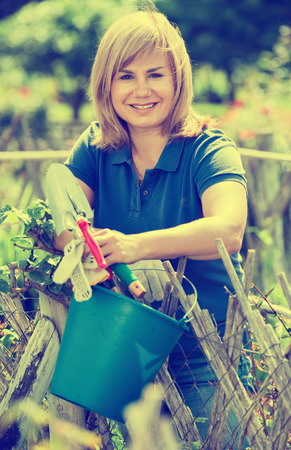 horticultural: Smiling blond mature woman  holding horticultural tools in garden on sunny day