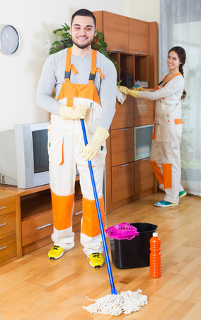 Positive professional young cleaners with equipment clean furniture of client house