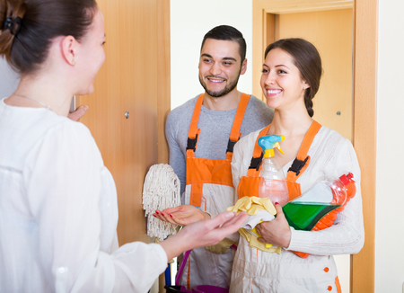 Housewife greeting cleaning service workers holding cleansers