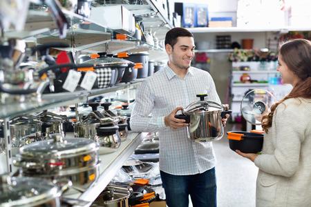 cookware: Pareja joven contenta positivo en la sección de utensilios de cocina en el hipermercado