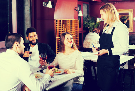 middle class: La gente feliz clase media disfrutando de la comida en la cafetería y hablando juntos