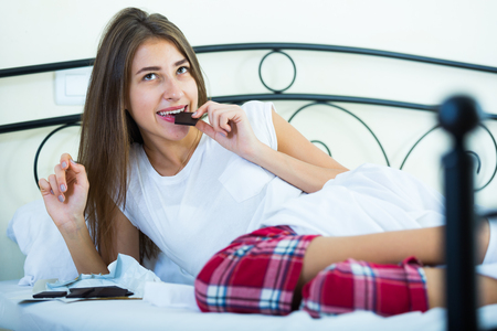 arousing: Happy girl sitting in bed and eating dark chocolate indoors Stock Photo