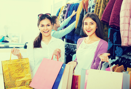 30s: Positive young people 30s choosing autumn clothes in shop Stock Photo